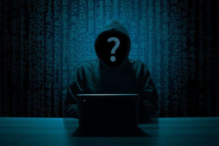 A hacker silhouette behind a computer.